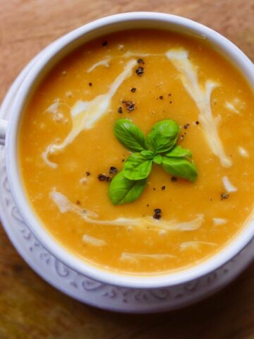 overview of soup with basil garnish in white bowl