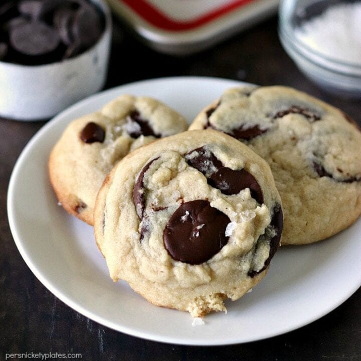Image of three chocolate chip cookies on a white plate.