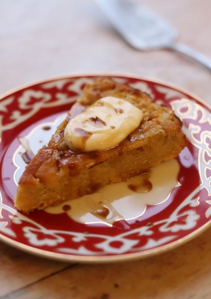 Slice of apple polenta cake with creme fraiche, on a plate