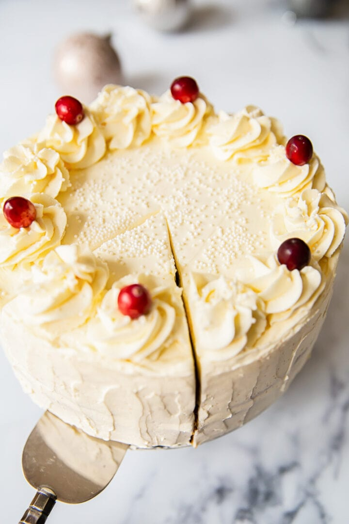 view of full white cake with one slice being served