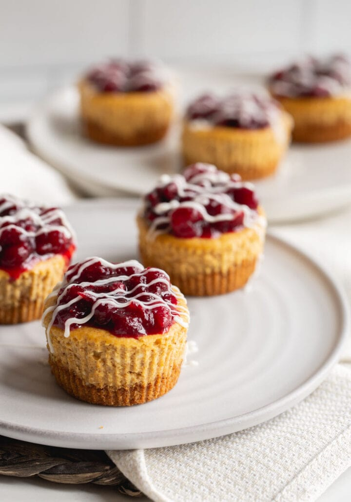 small cheesecakes topped with cranberry sauce on plates