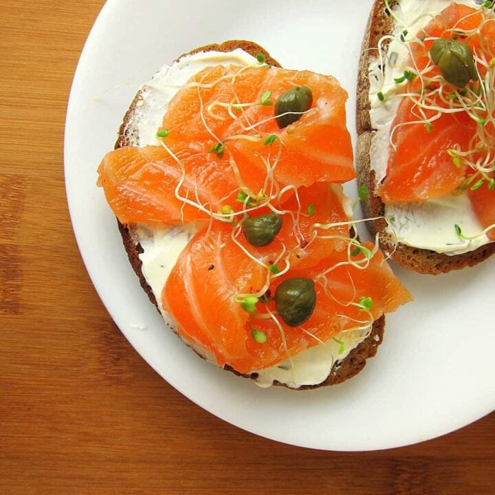 Image of salmon on slices of brown bread with cream cheese and capers.