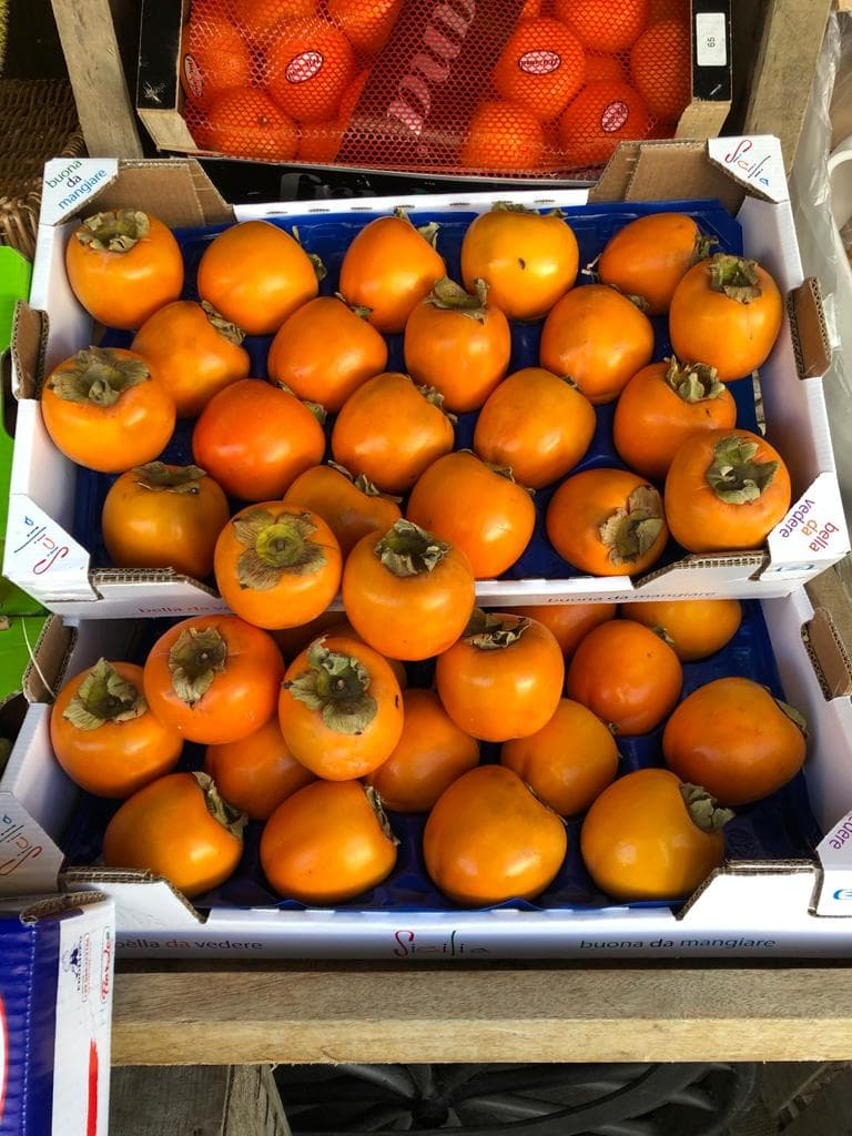 Box of persimmons outside shop
