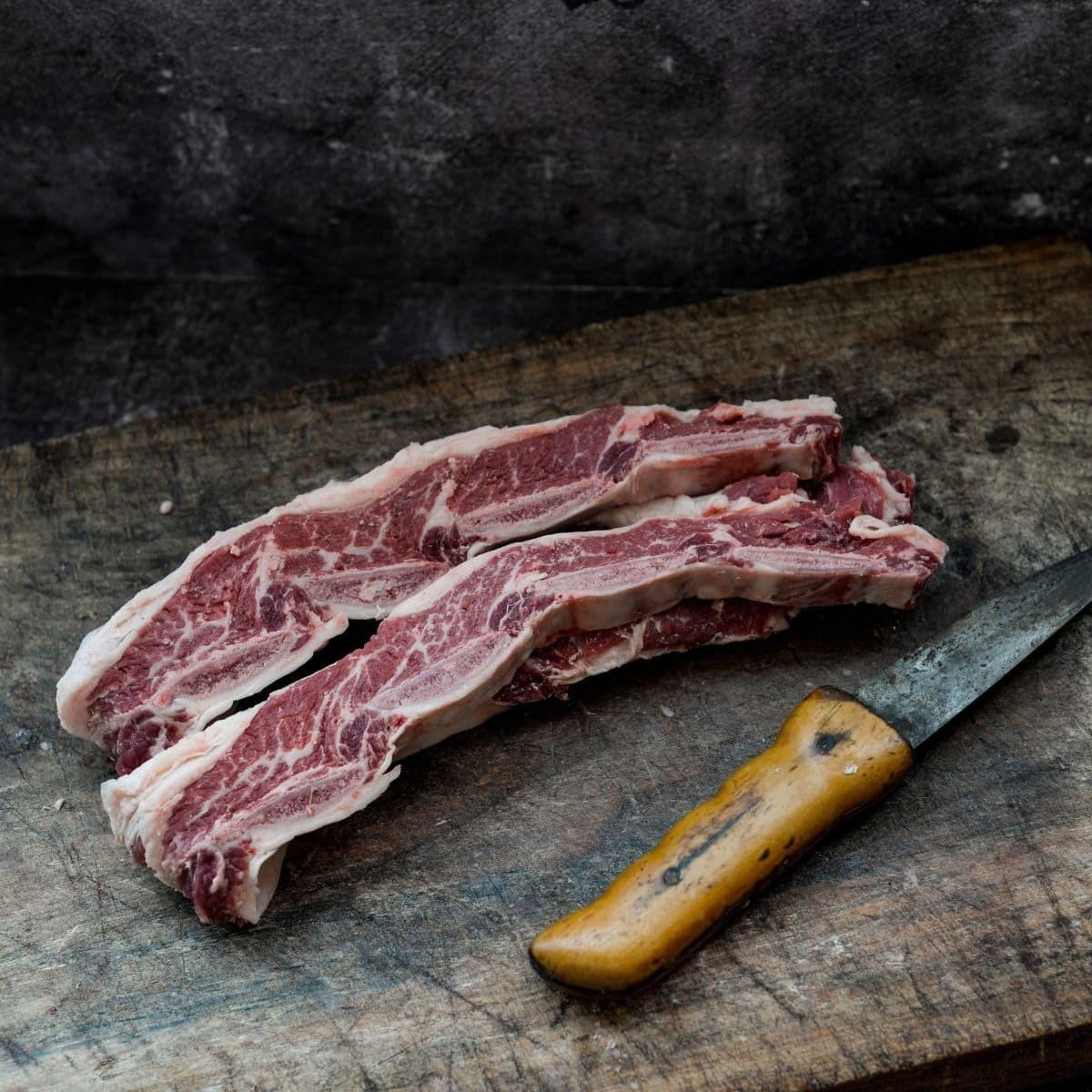 strips of meat next to a knife on chopping board