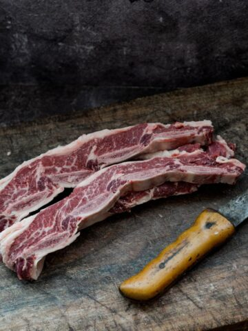 Image of cuts of meat next to a knife on chopping board.