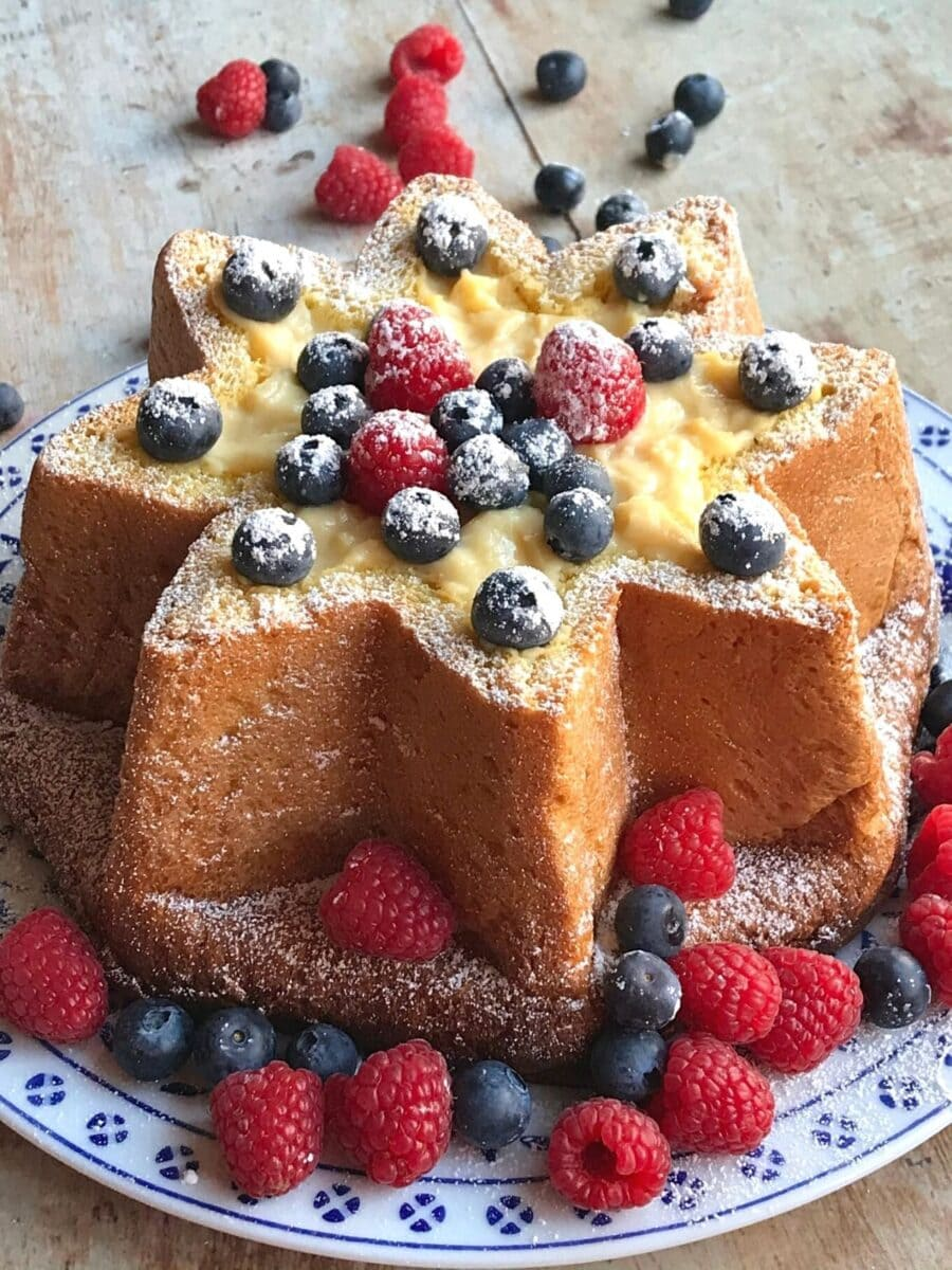 horizontal slice of pandoro filled with custard and berries