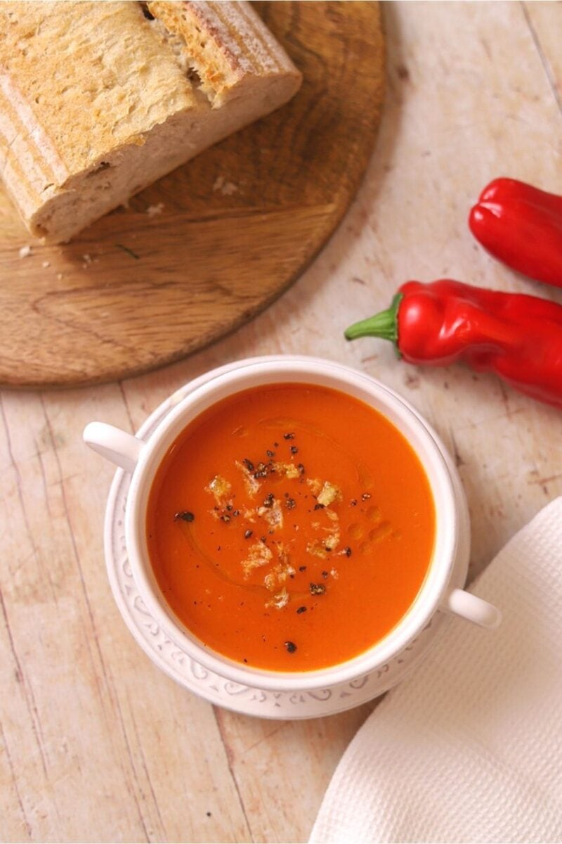 Overhead view of red pepper soup in white bowl