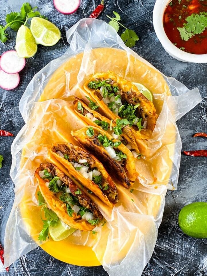 Image of birria tacos on a large yellow platter.