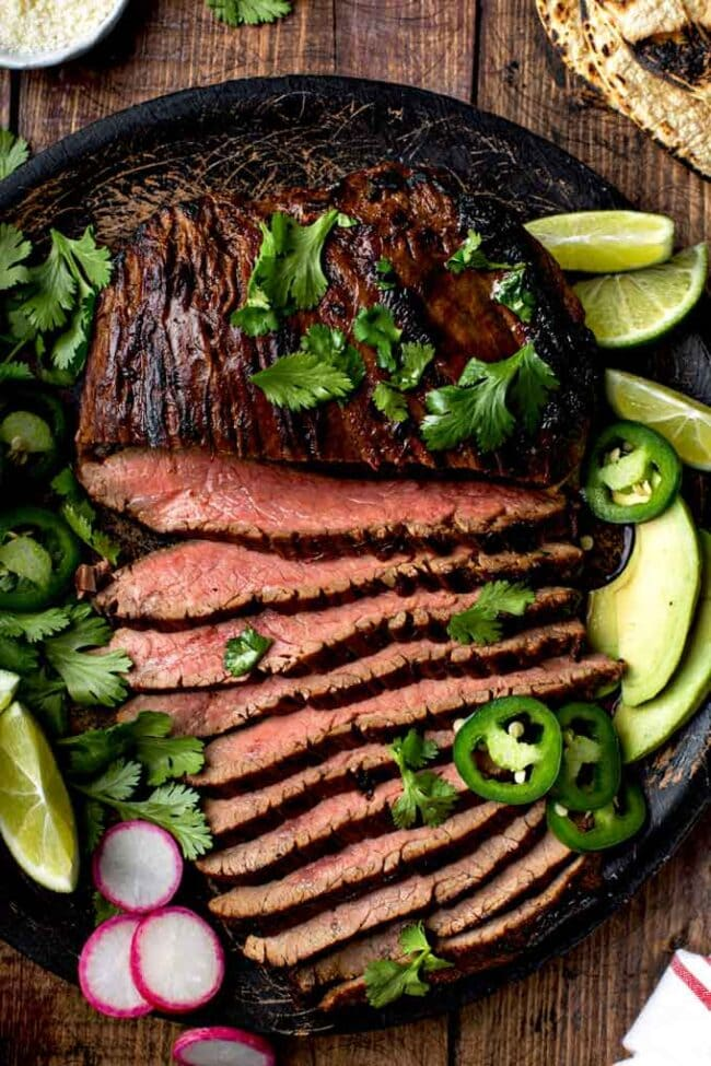 Image of partially sliced carne asada on a platter.