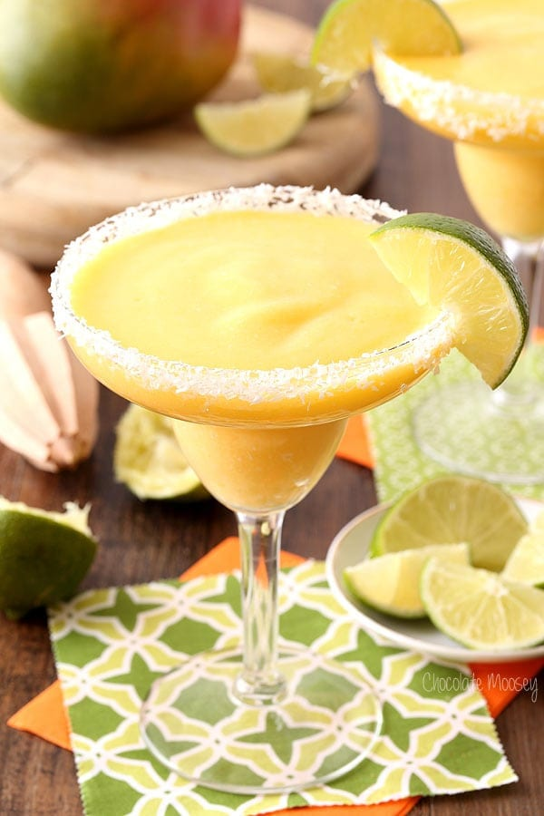 Image of two mango coconut frozen margaritas in a glass with slice of lime.
