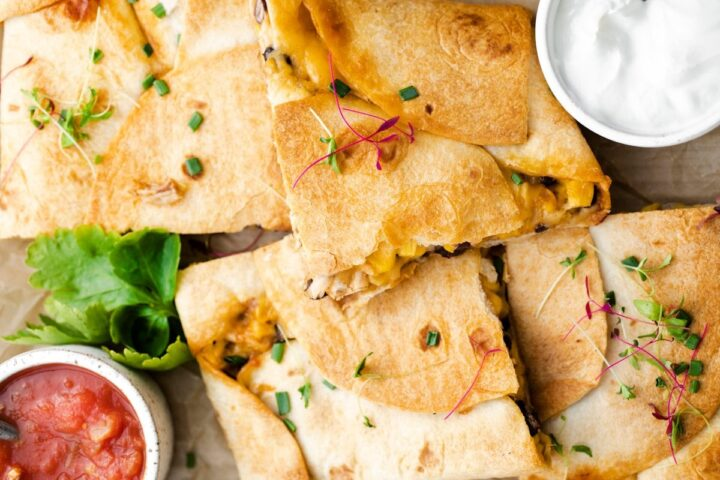 Image of squares of sheet pan chicken quesadillas with sauces.