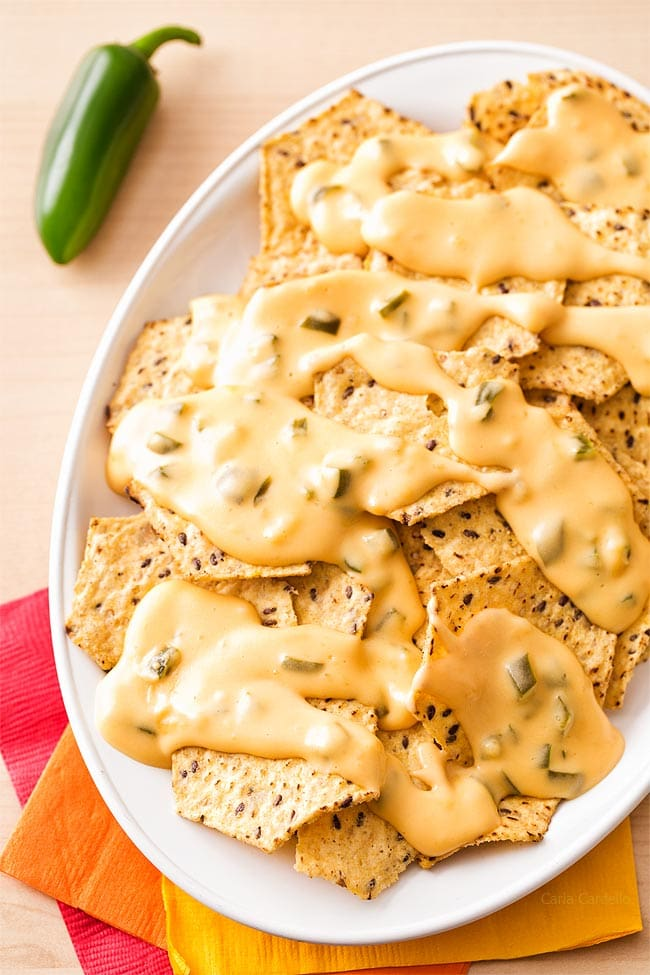 queso sauce over nachos on white platter