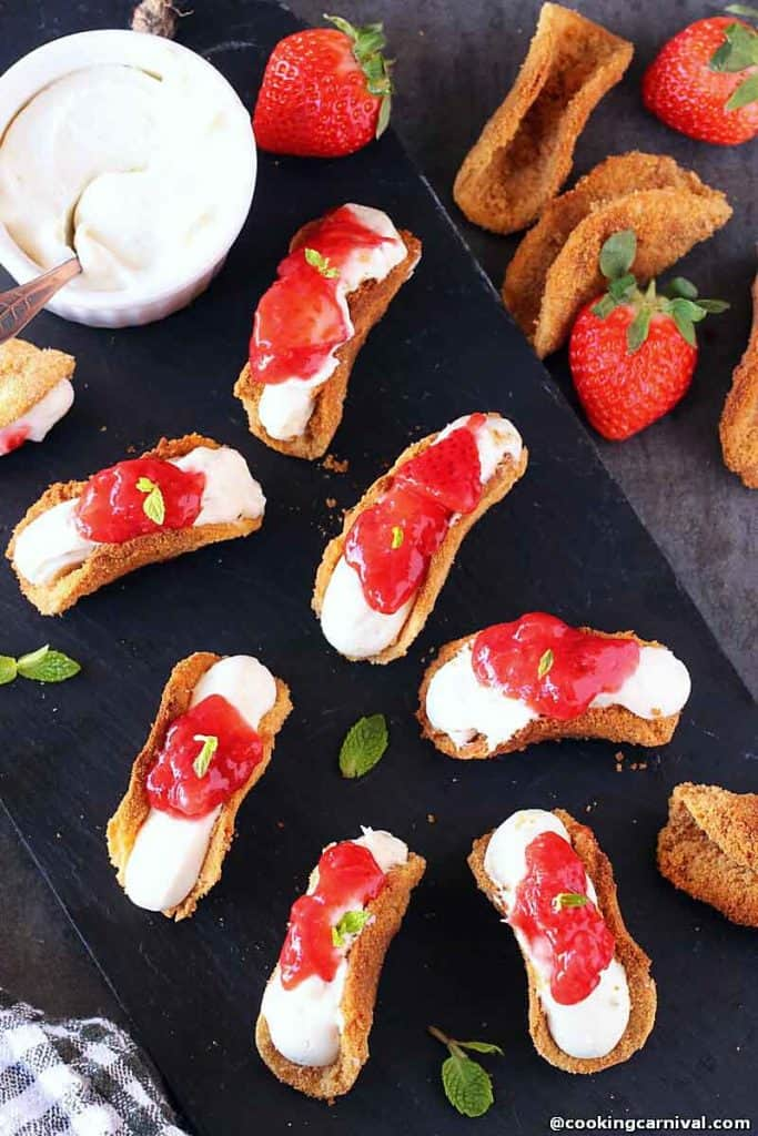 Image of mini strawberry tacos with bowl of cheesecake dip on black platter.