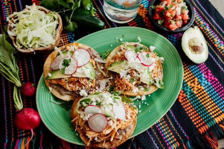 Three tortillas with chicken tinga and garnish on a platter