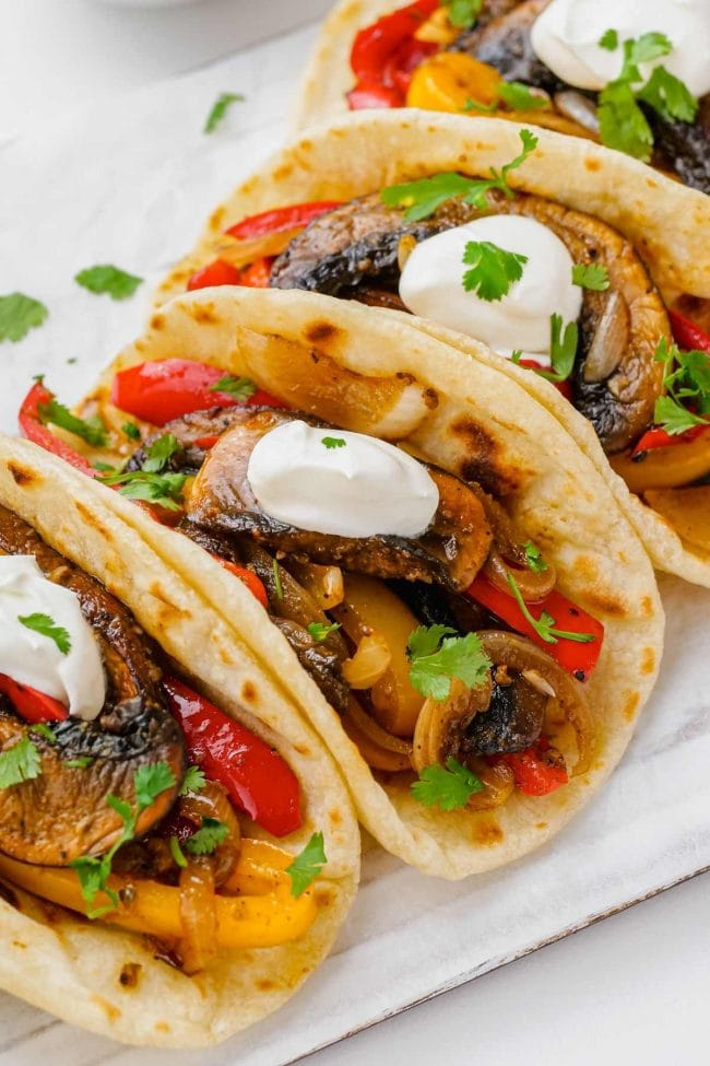 Image of vegetarian fajitas with sour cream arranged on a white platter.