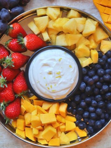 Image of fruit platter with small bowl of honey yogurt dip in the middle.