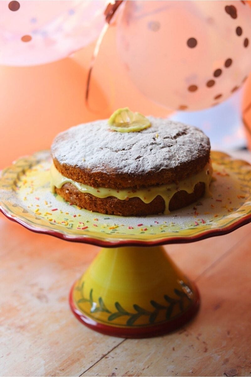 Banana cake on a cake stand, decorated with a slice of lemon and sprinkles.