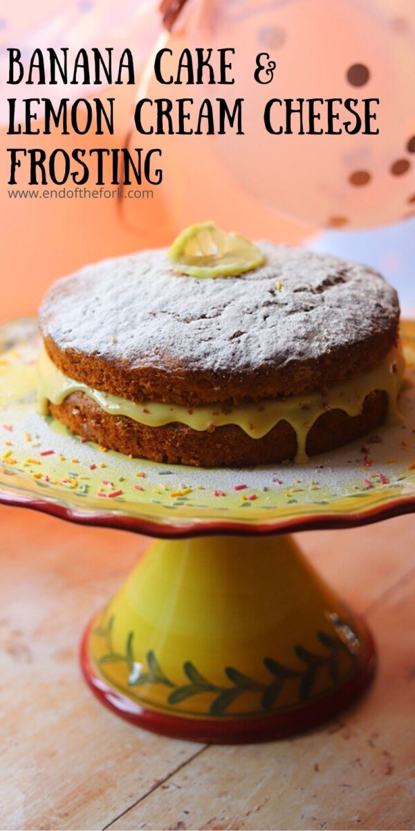 Pin image of banana cake with cream cheese frosting on a yellow cake stand.