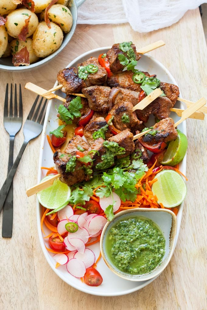 Image of beef kebabs and salad on white platter with mojo verde.