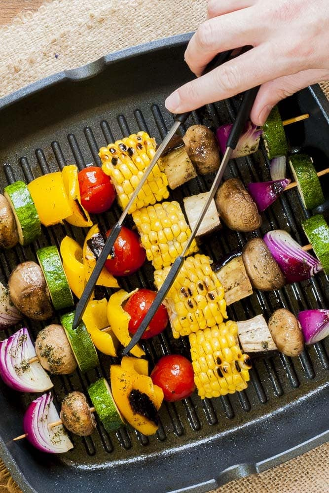 Image of four skewers of mixed vegetables on cast iron skillet.