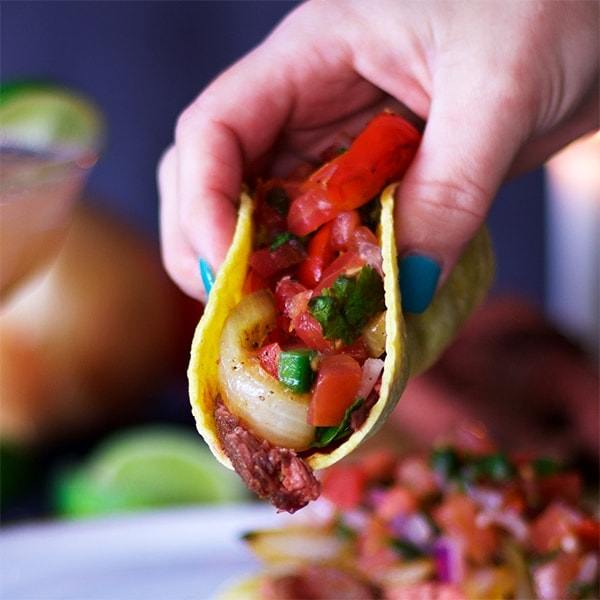 Image of hand lifting a taco filled with steak and pico de gallo.