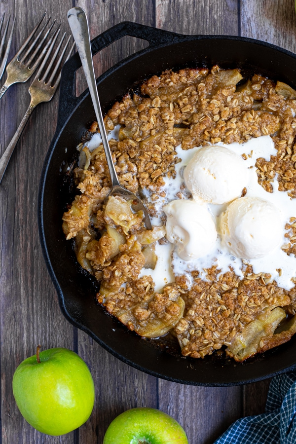 Image of apple crisp topped with three scoops of ice-cream in iron skillet.