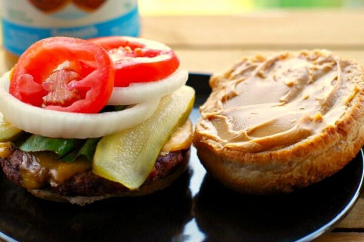Image of open burger showing spread of peanut butter on one half of the bun.