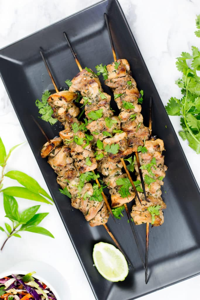 Image of six chicken skewers on black platter with lime.
