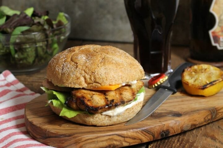Image of chicken breast burger with cheese on wooden board.