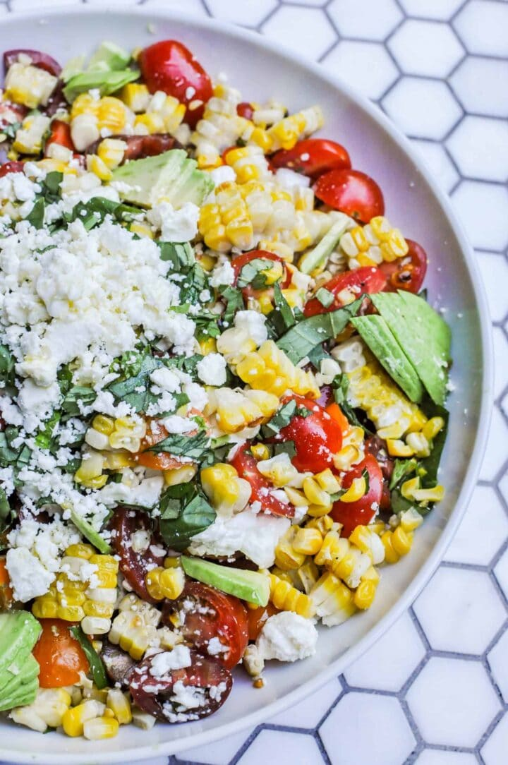Image of grilled corn salad with cheese and herbs on white plate.