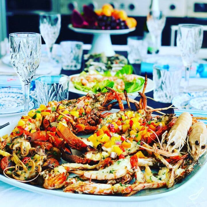 Image of platter of grilled lobsters on table setting.