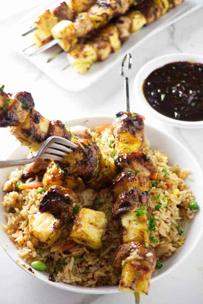 Image of chicken and pineapple skewers over vegetable rice in a large white bowl.