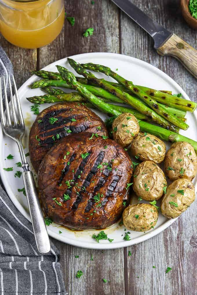 Image of two grilled portobello mushrooms on plate with asparagus and potatoes.