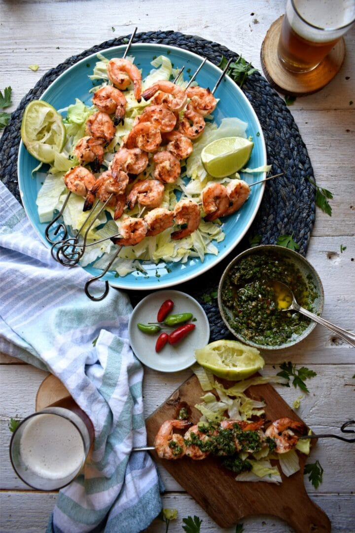 Image of plate of grilled shrimps with bowl of chimichurri.