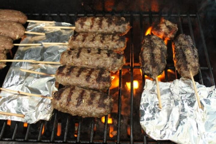 Image of kebabs on wooden skewers cooking on grill.