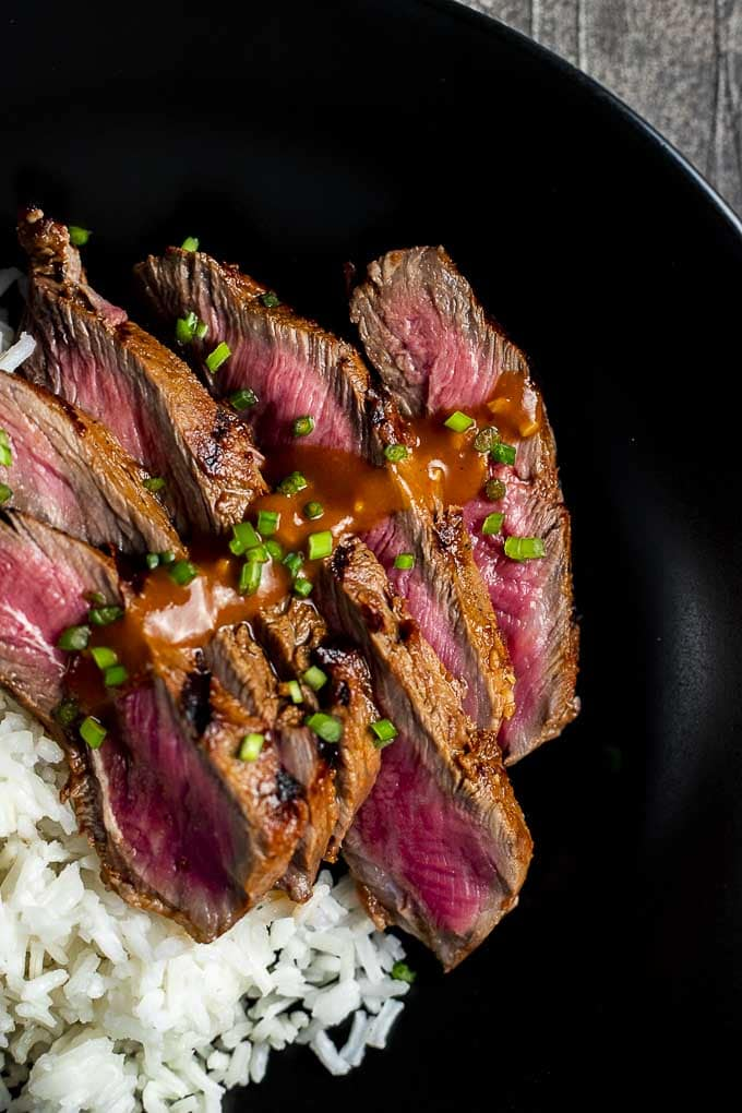 Image of strips of grilled beef garnished with gochujang sauce on black plate.