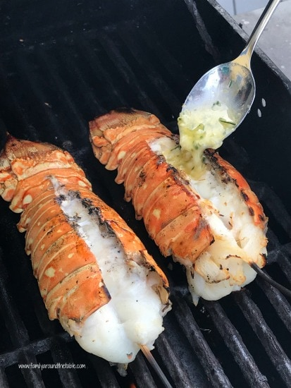 Image of two lobster tails on the grill being dressed with garlic butter.