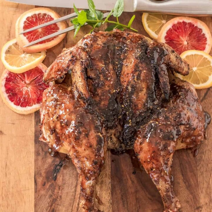 Image of a full butterflied grilled chicken covered in sauce on wooden board.