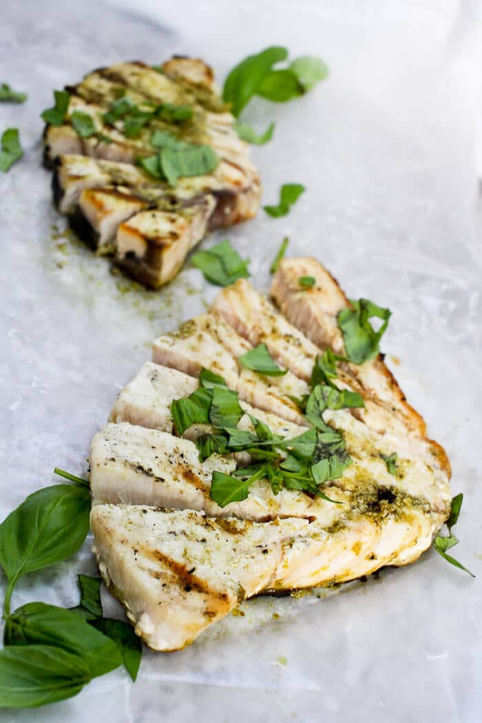Image of two cuts of grilled swordfish with pesto.