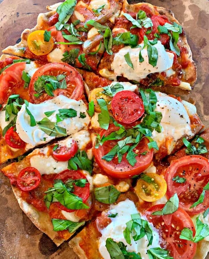 Image close up of grilled pizza cut into pieces.