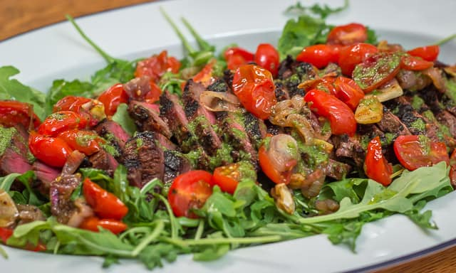Image of grilled flank steak with tomatoes on white platter.