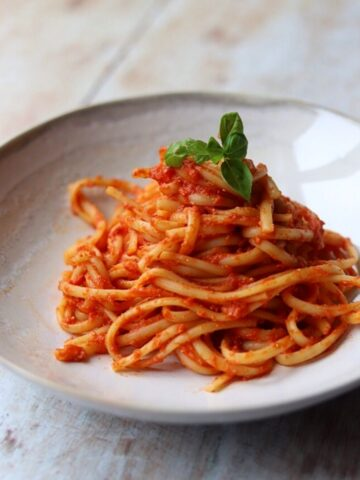 Image of Linguine with tomato sauce and fresh basil in white bowl