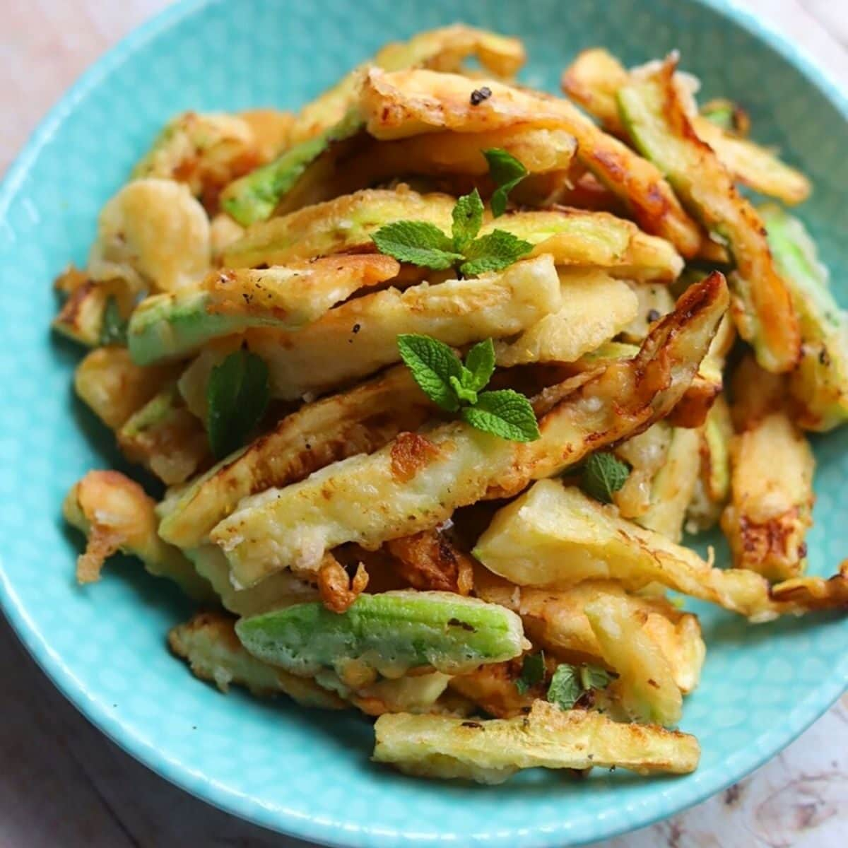 Plate of fried zucchini with mint leaves.