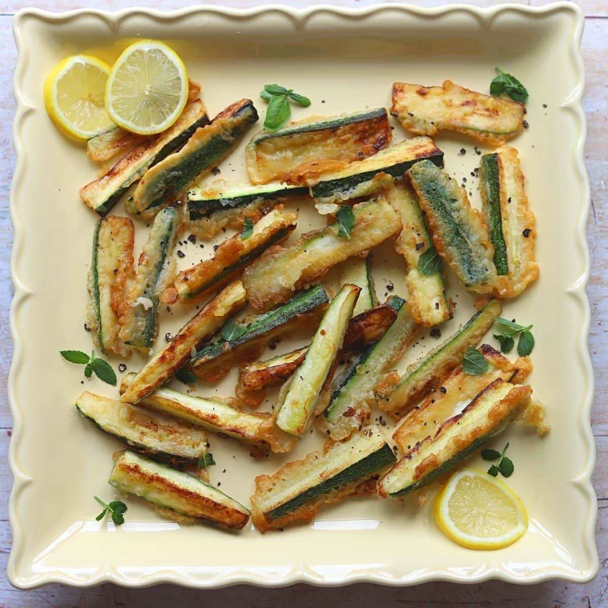 Fried zucchini chips on a large yellow platter with sliced lemon and fresh mint.