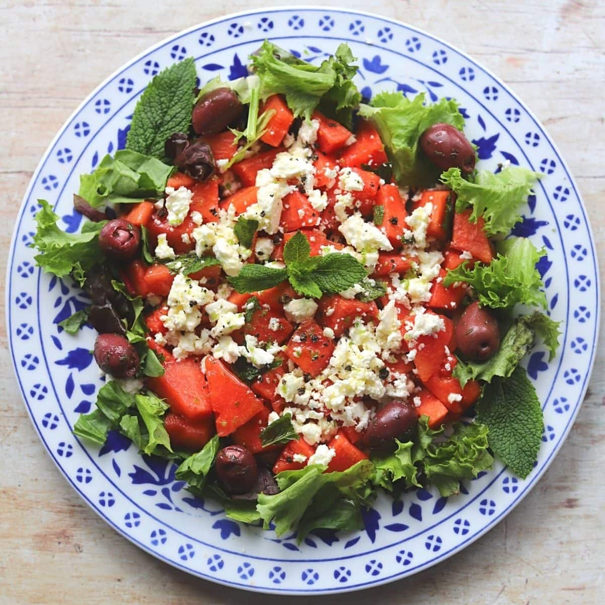 Watermelon feta salad with herbs on painted plate.