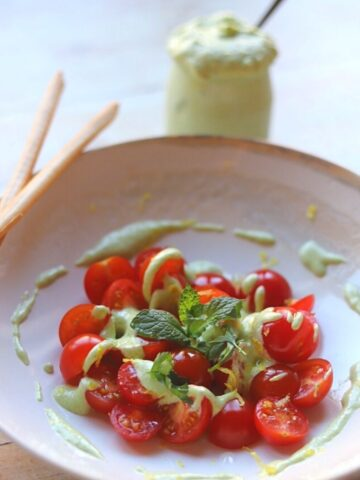 whipped feta dip over halved cherry tomatoes in a bowl