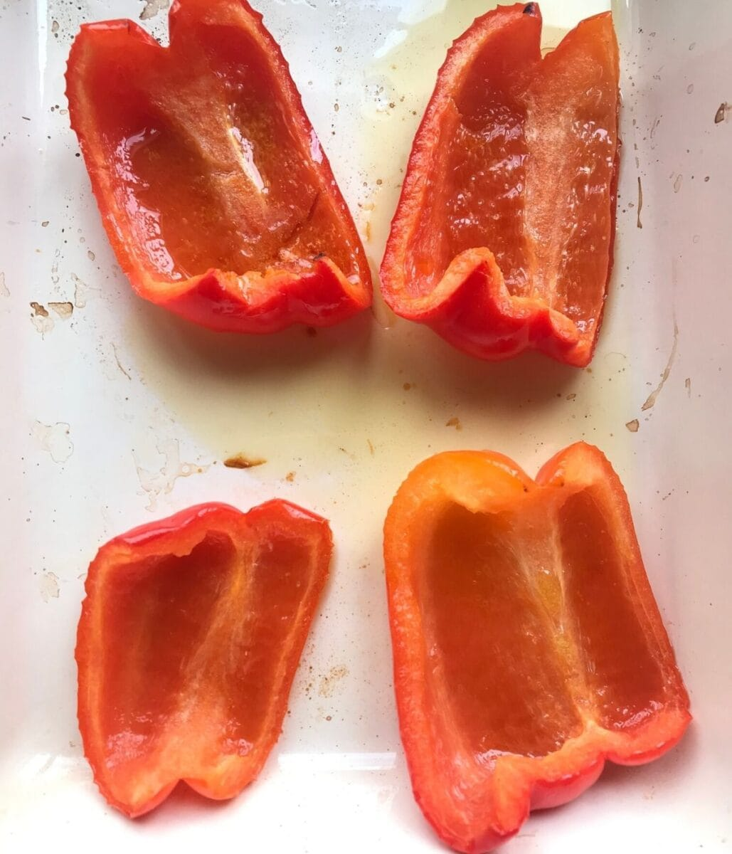 Grilled red bell peppers in pan with olive oil.
