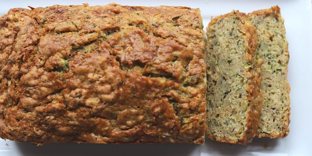 Whole loaf of zucchini banana bread partially sliced.